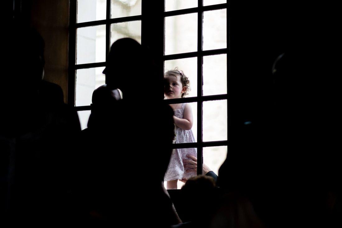 enfant qui observe la ceremonie civile derriere une fenetre