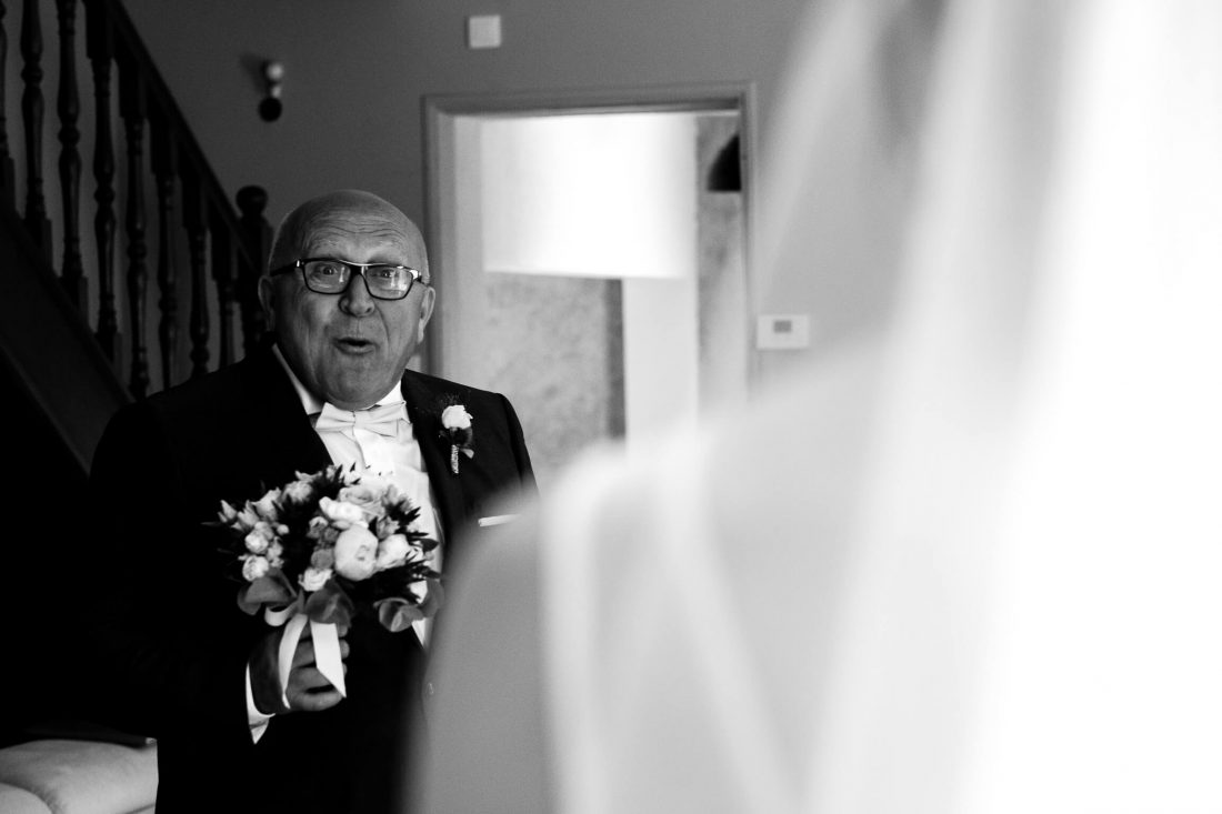 le pere de la mariee la decouvrant et lui apportant son bouquet