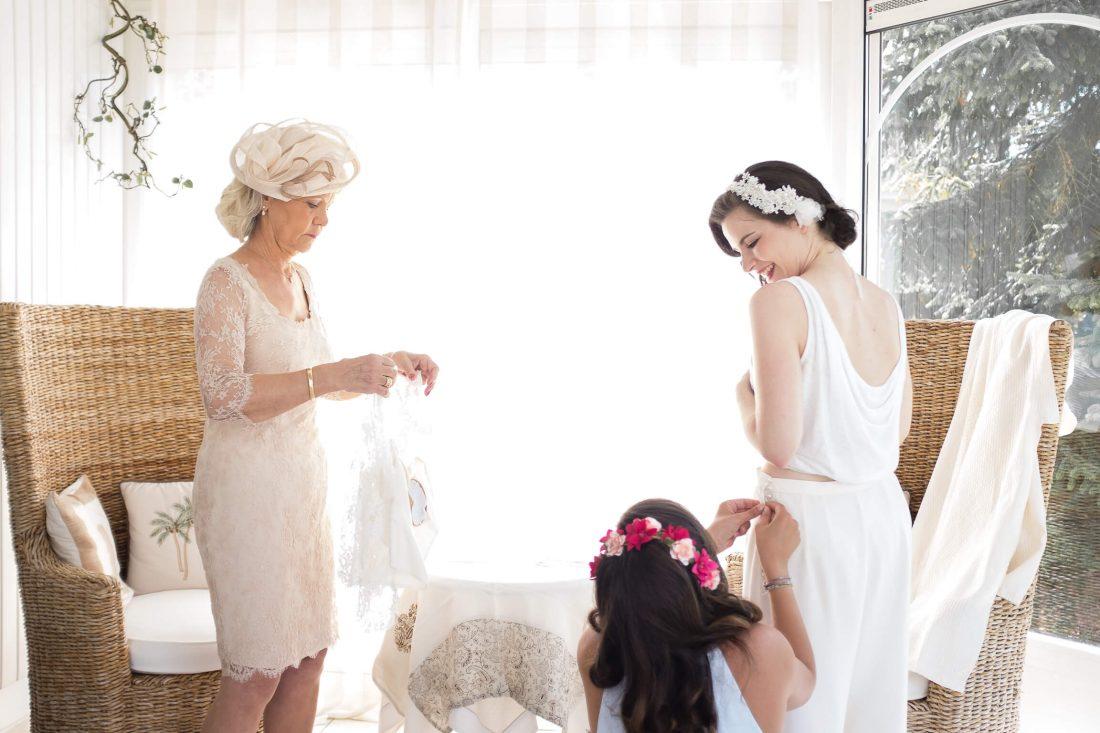 moment intime lors de l'habillage de la robe de la future mariee