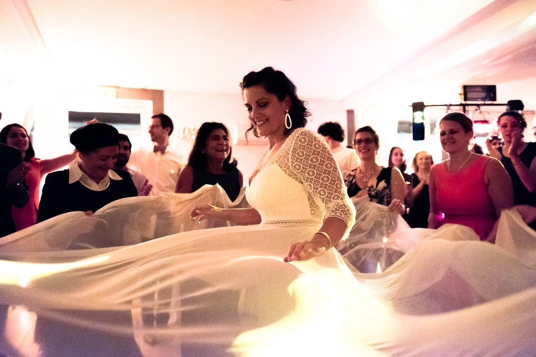 les femmes attrapent le voile de la robe de la mariee pour la faire danser comme le veut la coutume juive