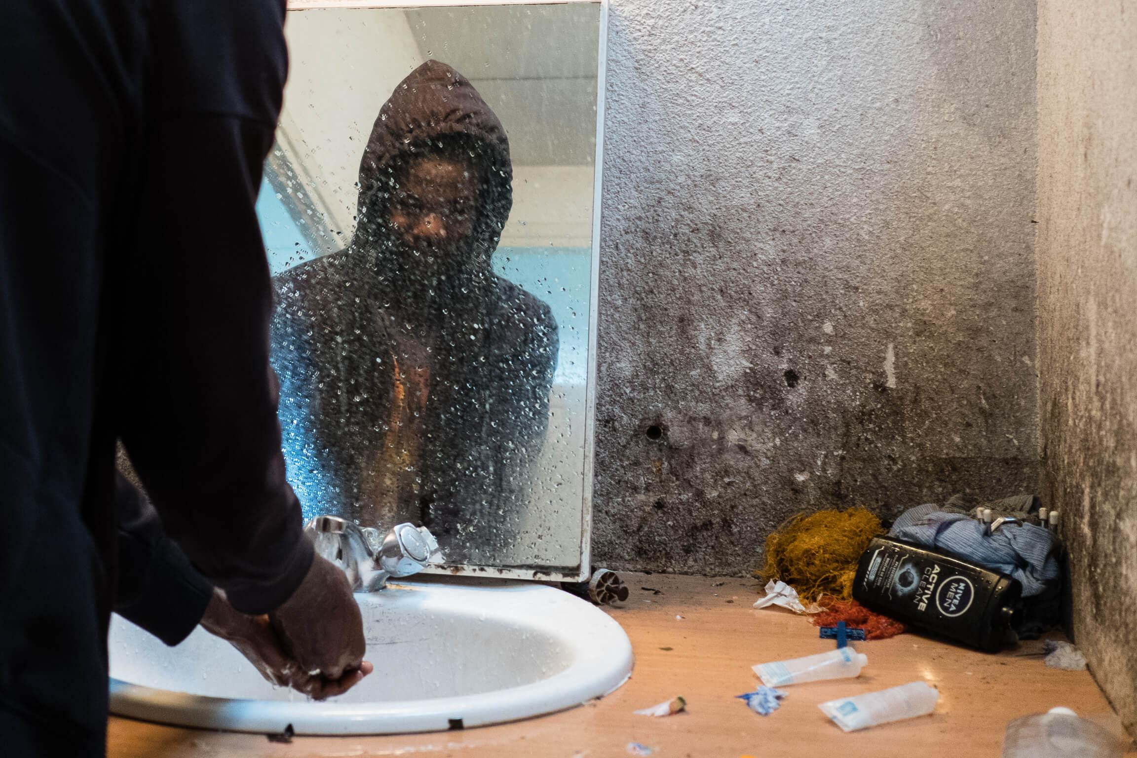 réfugié se lave les mains dans un squat qui a brûlé depuis