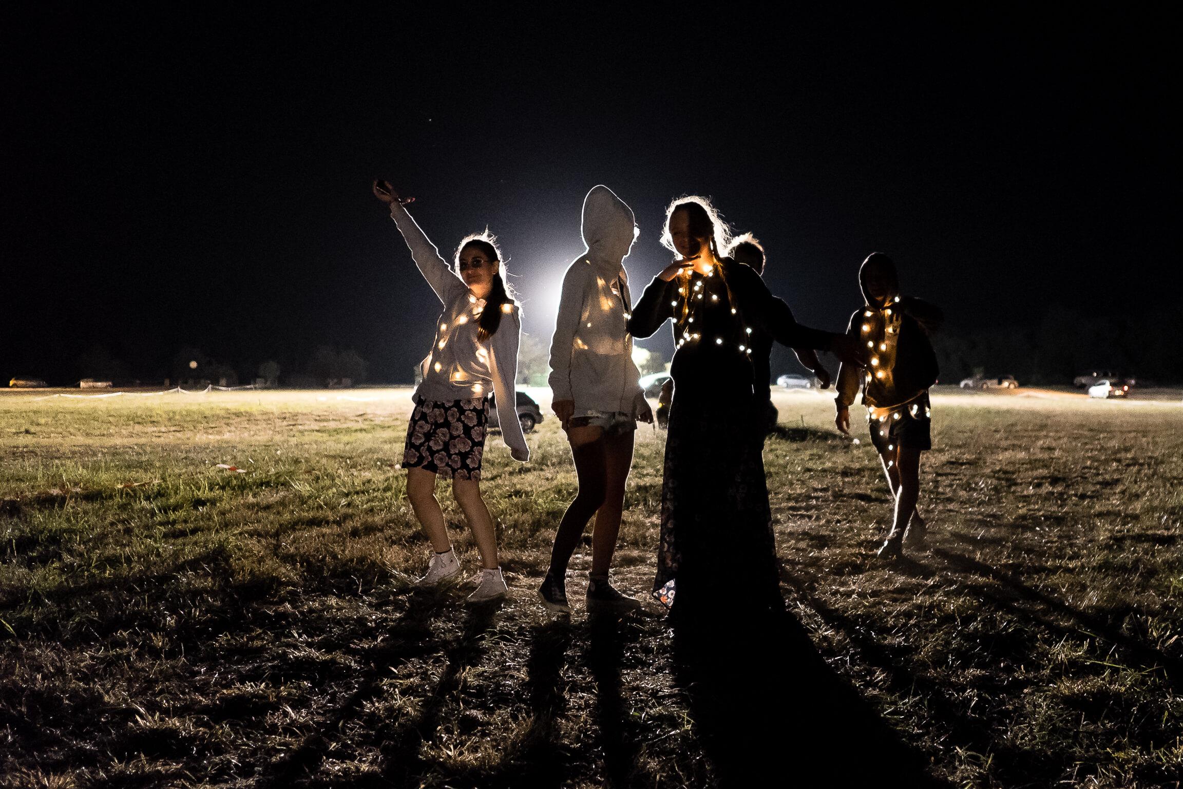 Ambiance au festival Terres du Son sur le parking avec des festivaliers lumineux